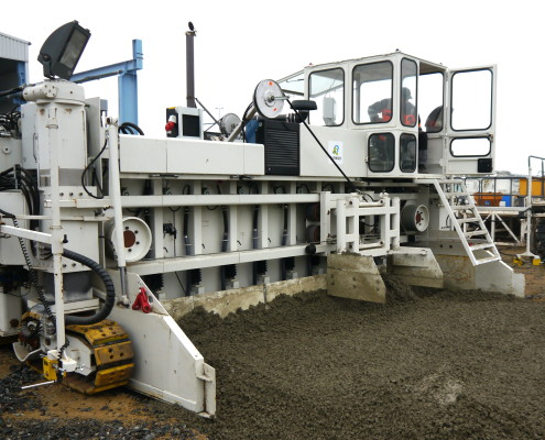 Fresh concrete is equally distributed in front of the paver. Vibrators compress the concrete and allow it to flow under the slip form.